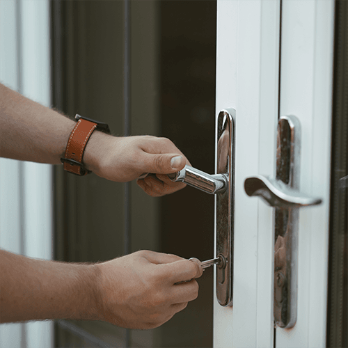 Person locking front door of home